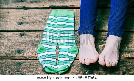 Bare female feet and green striped socks laying on the wooden floor. Closeup view