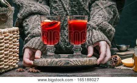 Human hands holding mulled wine in irish glasses on serving board. Rustic style. Front view
