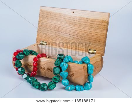 Picture of the opened light-coloured box for bijouterie with turquoise, malachite and coral bead necklaces isolated on white background. Handmade carved jewel box with beads. Side view.