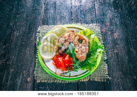 Cooked and garnished salmon steaks on the plate