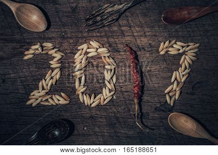 Paddy Was Arranged Word To 2017 A.d. With Wooden Spoon And Fork And Chilli On Old Wooden Background.