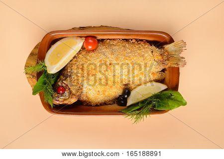 Fried crucian carp with lemon on light background