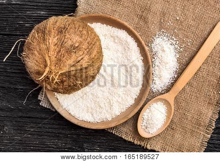 Coconut with desiccated coconut in a bowl and spoon on sack fiber.