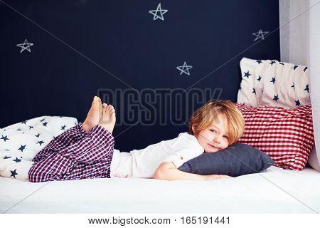 Cute Kid In Pajamas Lying In Bed