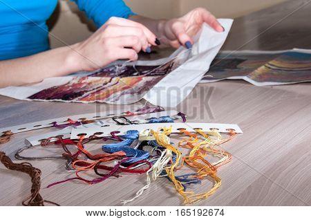 Female hand embroidered cross-stitch pattern under the scheme