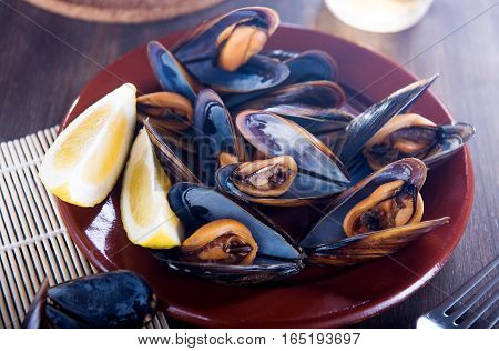 Fresh mussels with lemon on wooden background