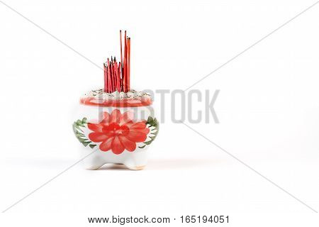 Burnt incense sticks in a ceramic incense burner on white background