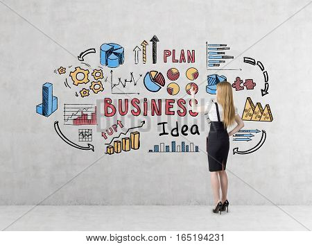 Rear view of a blond businesswoman in a black skirt drawing a colorful business idea sketch on a concrete wall