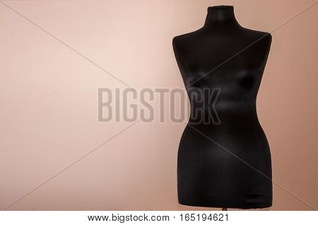 Black women sewing mannequin standing on a beige background