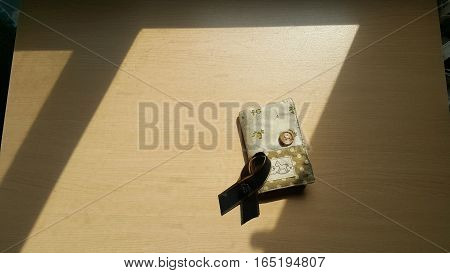 Black bow stack on the fabric card holder under the sun light.