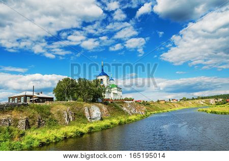 St. George Church on the rocky banks of the river Chusovaya on a summer day. Russia The Urals village Sloboda.