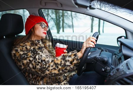Beautiful woman in a fur coat and red hat with red lips with coffee to go driving her car
