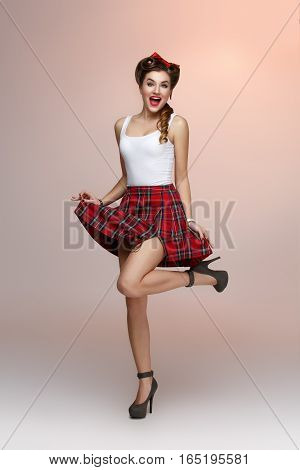 Beautiful young woman dressed in pin up style with retro makeup and hairstyle standing. Full body studio shot over beige background.