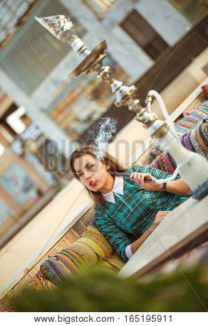 Beautiful young woman smokes a hookah in a cafe Egypt