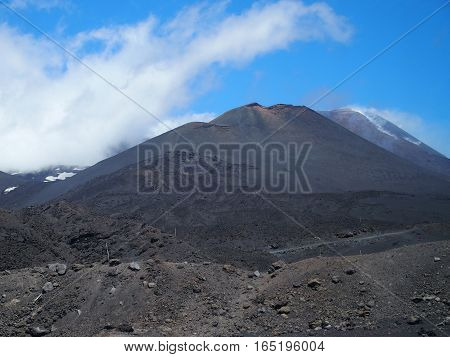 MOUNT ETNA, bbandoned fuming crater in SICILY at ITALY, tallest active volcano in EUROPE with cloudy blue sky in warm day on MAY