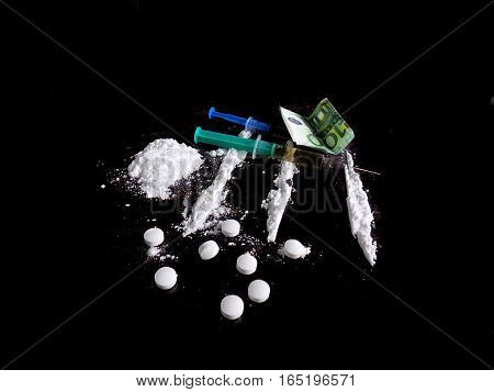 Injection syringe on cocaine drug powder lines, cocaine pile and pills and euro money bills on black background poster