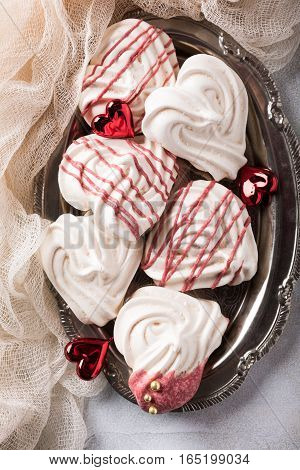 Homemade meringues in heart shape on old metal plate for Valentine's day, top view, copy space.