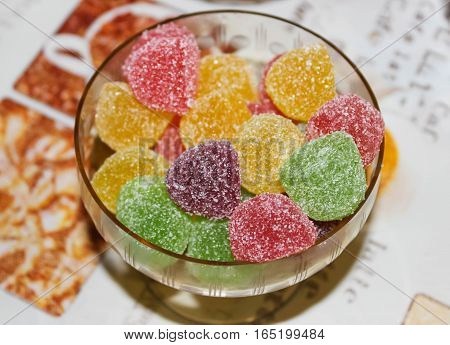 Multi-colored fruit jelly in a vase on a table