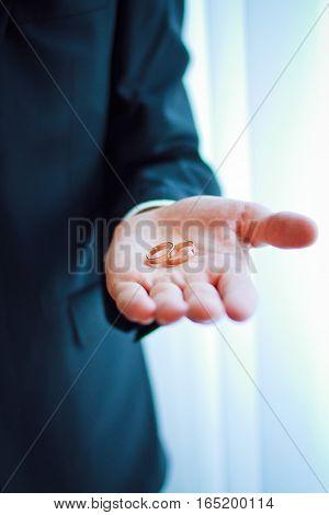 Groom hand holding gold wedding rings, DOF focus on rings.