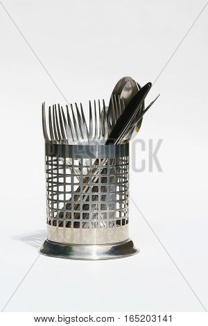 Cutlery in a metal basket on a white background