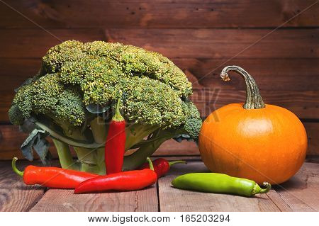 Fresh healthy useful vegetables broccoli, pumpkin, peppers on wooden table close up. Purple and vintage tinted