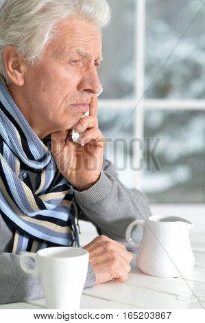 Portrait of a mature man drinking tea feeling bad