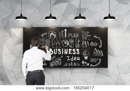 Rear view of a young businessman in a white shirt drawing a business idea sketch on a blackboard in a room with geometric pattern on the walls.