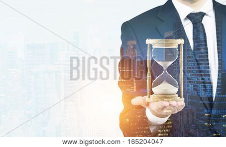 Close up of a businessman holding hourglass. Office. Morning cityscape. Concept of time management. Mock up. Toned image. Double exposure