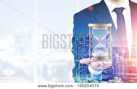 Close up of a businessman holding hourglass. Office. Night cityscape. Concept of time management. Mock up. Toned image. Double exposure