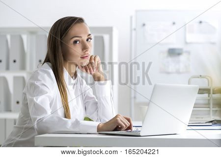 Serious and slightly sad businesswoman in a white blouse is sitting at her workplace in a white office and looking at the viewer