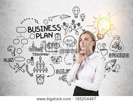 Portrait of a blond businesswoman in shirt with a hand on the chin standing near a concrete wall with a business plan sketch and a shining light bulb