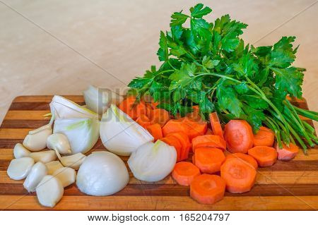 Fresh Onion, Garlic,  Carrot And Parsley On A Kitchen Tray