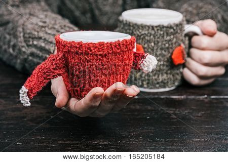 Human hands holding big and small mugs in wool warmers. Front view