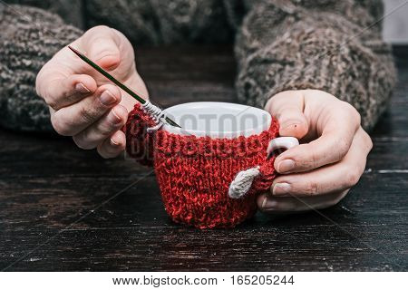 Human hands holding little cup in wool warmer with unfinished sleeve. Front view