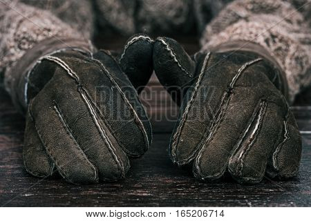 Human hands in winter gloves on the wood table. Front closeup view