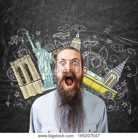 Portrait of a screaming young man with a long beard standing near a blackboard with New York sights drawn on it.
