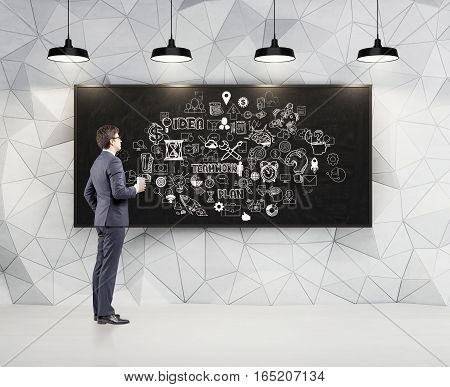 Side view of a businessman with a paper coffee cup looking at a large white business team sketch drawn on a blackboard. Geometric wall pattern. 3d rendering