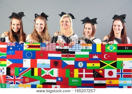 group of cheerleaders holding poster with flags. flags are from the CIA world factbook, public domain