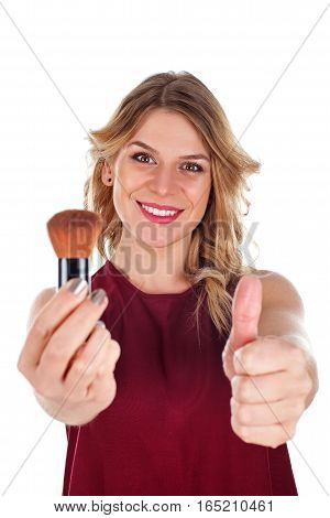 Picture of a beautiful woman holding a powder brush showing thumb up