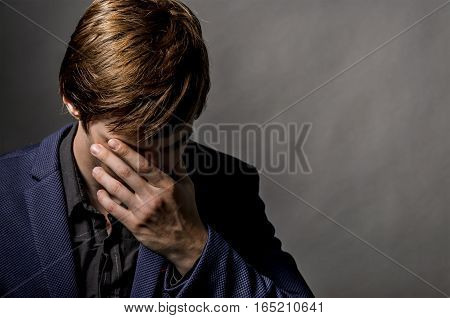 young businessman in a suit sad and feels pain in head the dark. Hand holding head and fingers visible