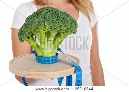 Close up picture of a fresh broccoli and a measurer in a woman's hands
