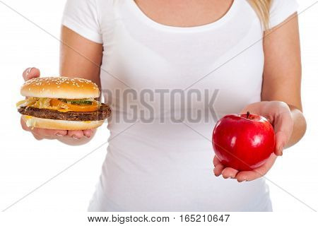 Picture of a woman holding a hamburger and a fresh apple