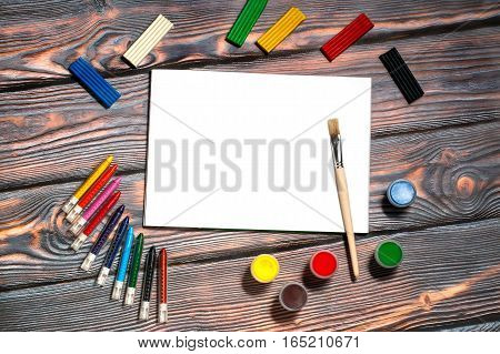 School supplies for kids - drawing album, brush, wax crayons, finger paints and plasticine, copyspace, rustic wooden background