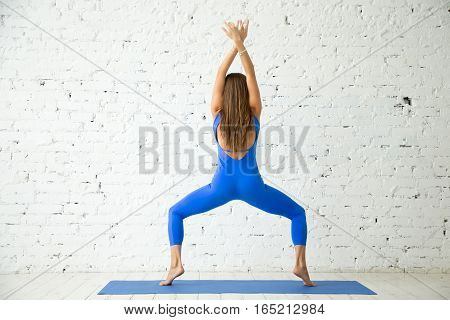 Young attractive woman practicing yoga, standing in Goddess exercise, Sumo Squat pose, working out, wearing sportswear, blue jumpsuit, indoor full length, white loft studio background, rear view