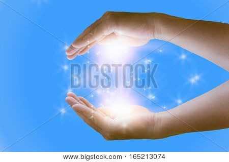 Opened magic hand with magic lights on blue background