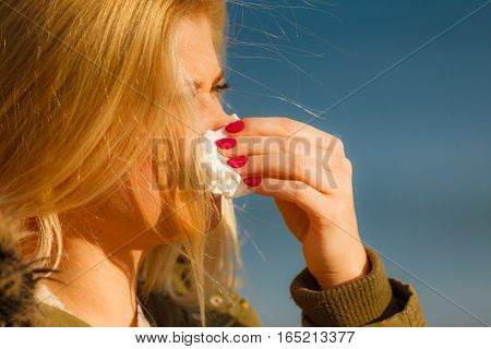 Seasonal flu cold runny nose concept. Sneezing blonde young woman into tissue outside sunny winter shot