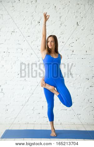 Young happy attractive woman practicing yoga, standing in Vrksasana exercise, Tree pose, working out, wearing sportswear, blue jumpsuit, indoor full length, white loft studio background