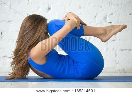 Young attractive woman practicing yoga, Knees to Chest exercise, Apanasana pose, working out, wearing sportswear, blue suit, full length, white loft studio background, way of heart tattoo