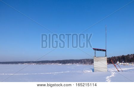 Lifeguard tower on the beach of frozen sea covered in snow, Siberia, Russia