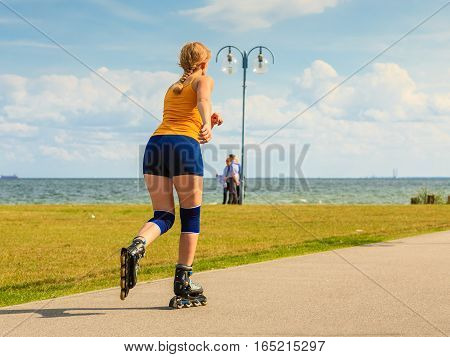 Holidays active lifestyle freedom concept. Young fit woman on roller skates riding outdoors on street girl rollerblading on sunny day